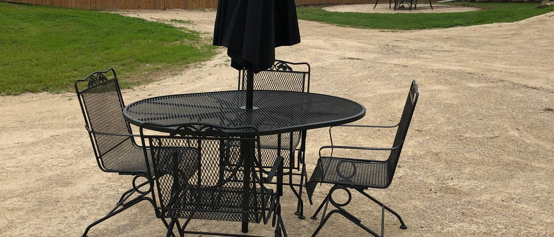 3 black patio tables with solar lit umbrellas