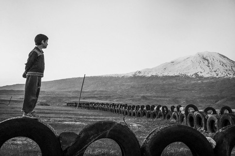A Wall around His Home. There is an important border crossing between Turkey and Iran by Mount Ararat. Every day hundreds of big trucks pass through this crossing. When they tear their tires, they leave them on the road and the villagers collect them to make walls around their homes. Doğubeyazıt, Turkey 2015