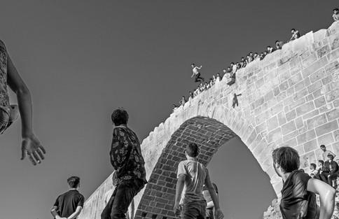High Dive into the Khabur River From an ancient bridge, teens leap 16 meters down to the Khabur River. Zakho, Iraq 2019