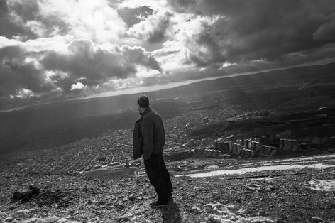 The man is looking to the city view from the mountain. Sulaymaniyah, Iraq 2019