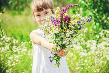 child-with-bouquet-wildflowers-selective