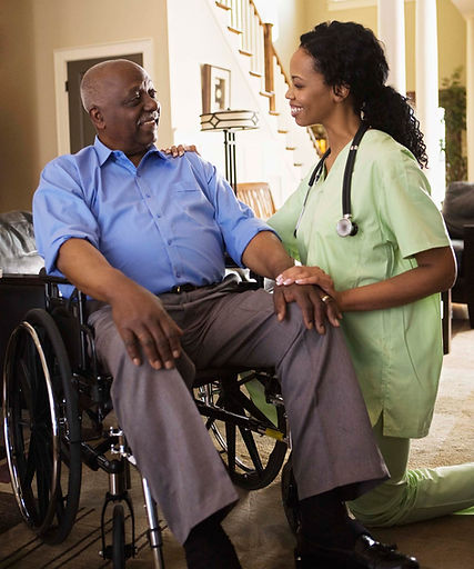 A caretaker interacting with an elderly man in a wheelchair in his home