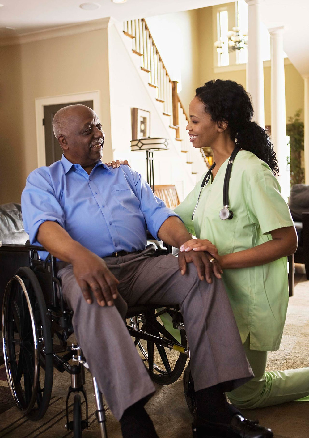 Man in wheelchair with home care nurse at his side.