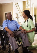 elderly black man being assisted by a black nurse