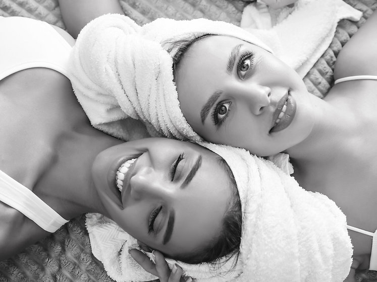 two-young-beautiful-smiling-women-in-white-bathrobes-and-towels-on-head.jpg
