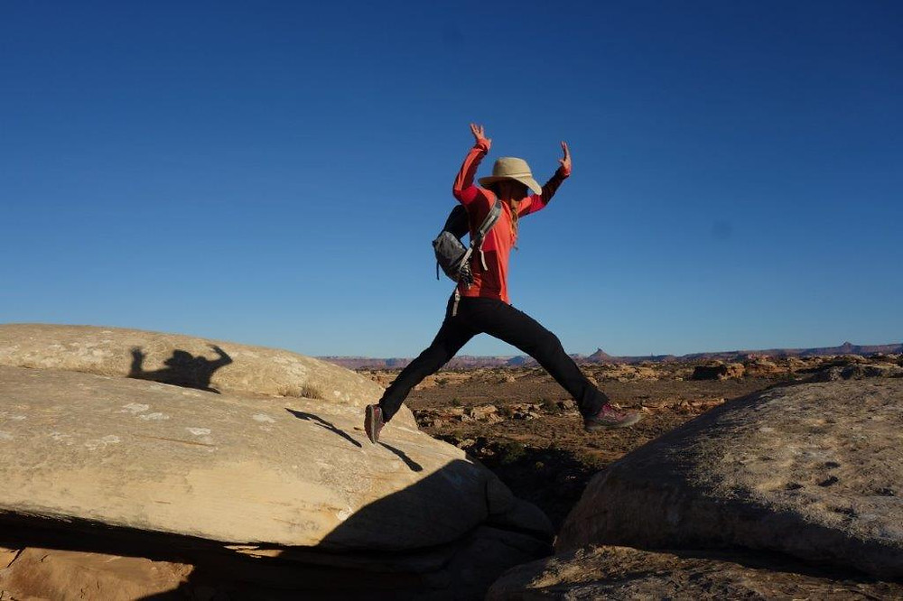 Malia jumping over crevice in rocks
