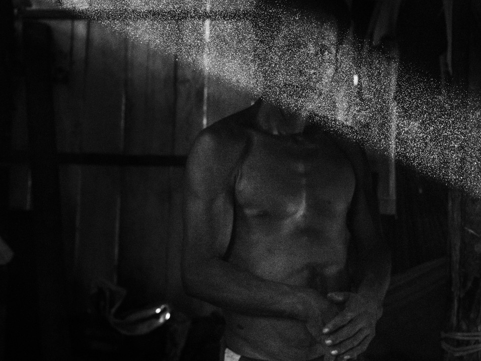 In October, 2018, Aladino stands alone in his house, the village of Pebas, Amazon region, after preparing a considerable amount of coca powder for the week. He also has his hands over the scar on his belly revealing that he is still in pain even after more than a year of his surgery. The prescription after the procedure was to abandon the consumption of the powder but being his most important element for healing and being a shaman, he cannot do it. The cultural crusade is disturbing Aladino and putting him in a position to choose between his health or his cultural duty.