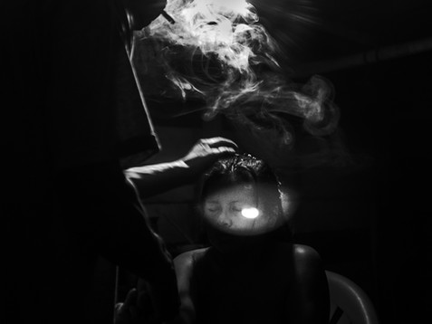 In May, 2017, Aladino, a native Bora shaman, blows smoke on his patient's head during one of the healing sessions late at night. The house is located in Pebas, a small village in the Amazon. Before blowing the smoke, he performs a prayer in Bora language and asks the spirits to guide him throughout the process. The spiritual process is to make a woman called Marili, who feels sick from her stomach and is facing trouble sleeping, better again. Aladino says that the duty of a natural healer is to work with all kind of diseases from headaches, which can take a day, to the worse like malediction, which can take weeks.
