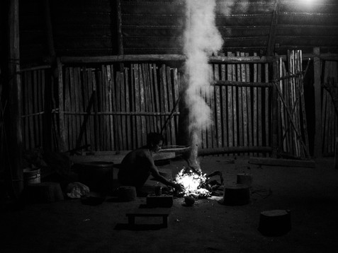 """In April, 2018, Aladino, a native Bora shaman, is alone preparing the elements for a night session of connection with the spirits. He is inside a """"maloca"""", a sacred collective house for the indigenous communities located in the village of Pebas, Amazon region. At the moment, he is burning some dry leaves to be offered to his Bora Gods of Coca."""