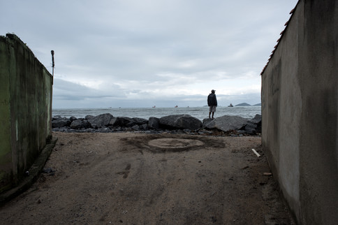 On July 30th, 2020 a man watches the horizon with a few oil ships waiting for a space in the local harbor.