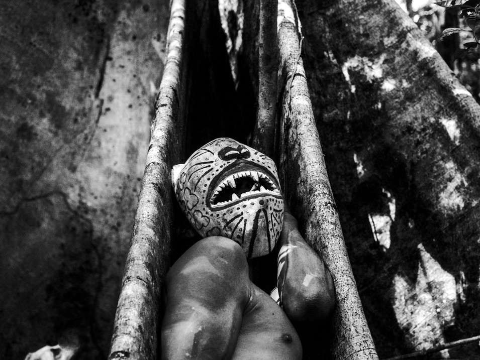 In April, 2018, Aladino, a native Bora shaman, wears his spotted jaguar mask while smoking on the roots of a tree in the Amazon. The mask was made by himself with a piece of wood from a special tree for the Boras. The region is still a virgin forest and the Boras, Aladino's ethnic group, consider it a Sacred Valley. The transformation is necessary to ask permission to be there and to connect with all the living beings that populate the region.