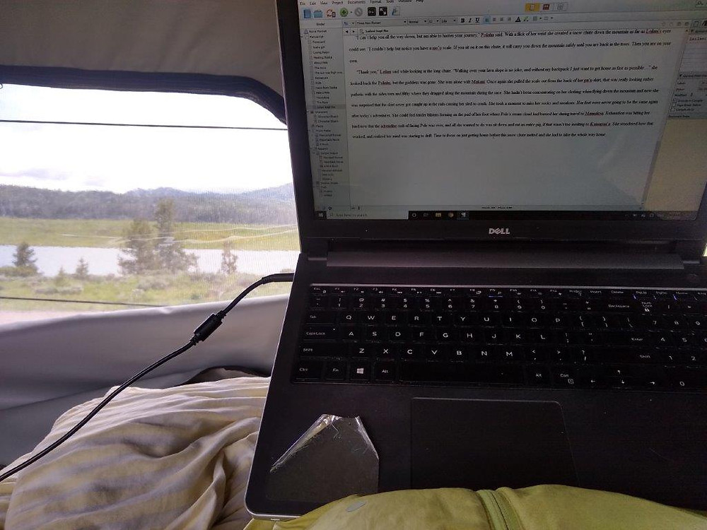 Laptop and view of lake from campervan window