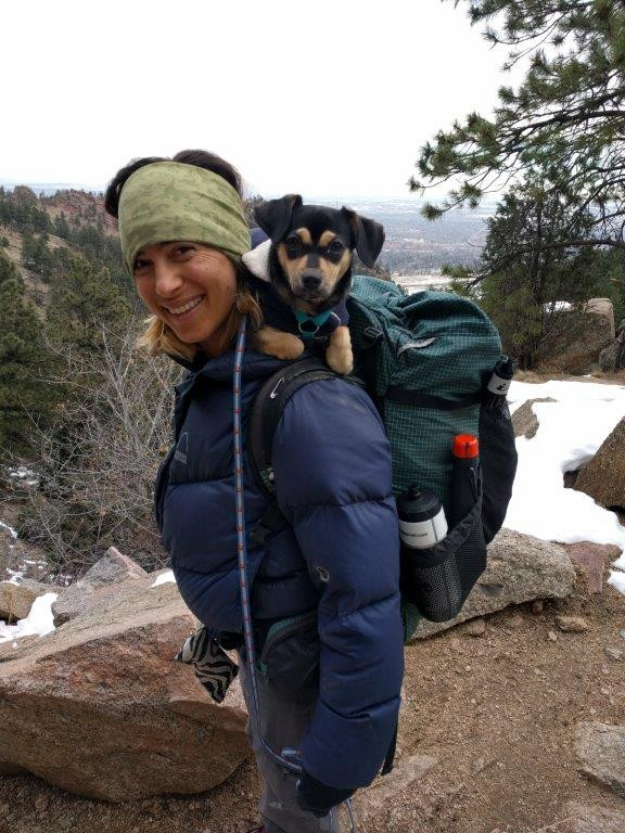 Malia with puppy on her backpack during a hike
