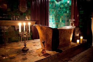 An athmospheric pictures of a home renovation with a cupper bathtube and dark green tiles.