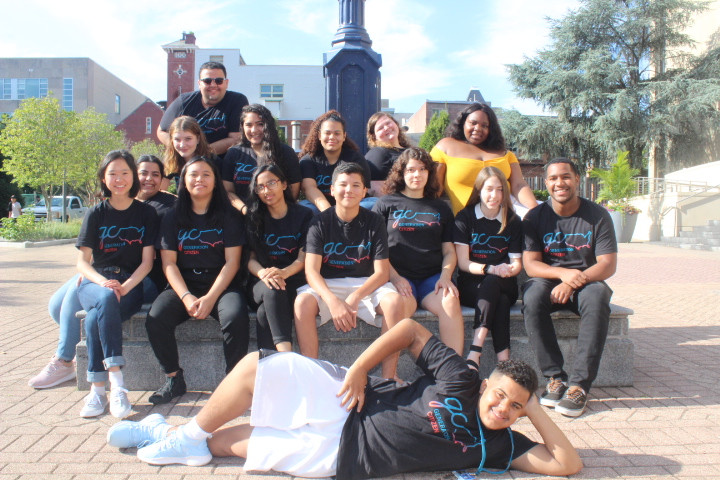 A group of students sit together wearing matching shirts.