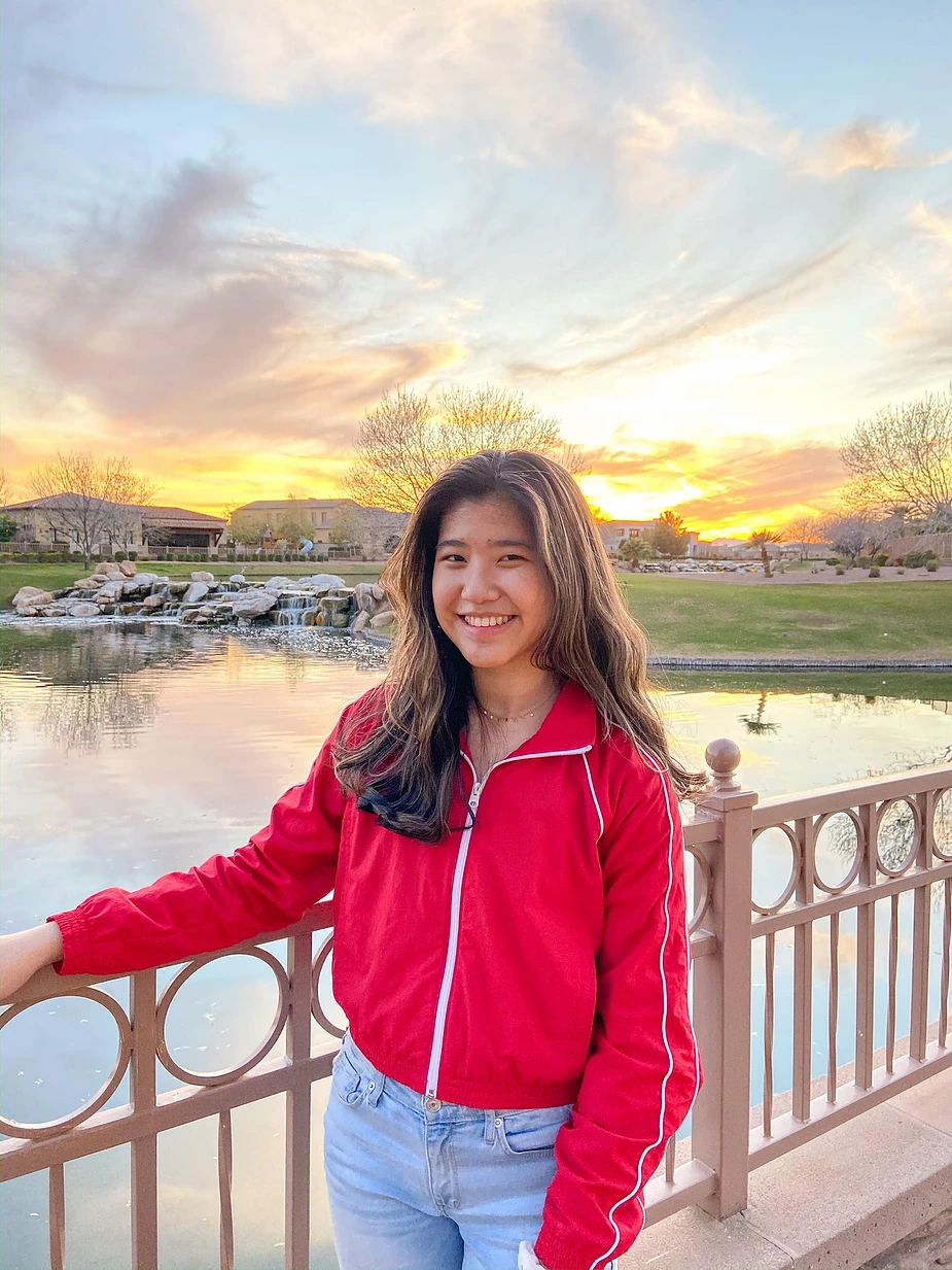 Katherine Wei a young people has a broad smile on her face as she stands on a bridge. Behind is a small body of water, a beautiful sunset fills the sky with beautiful colors.