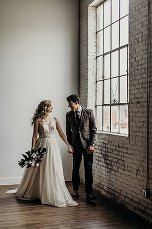 Bride and groom in front of industrial window