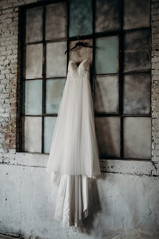 wedding dress hanging on industrial windows
