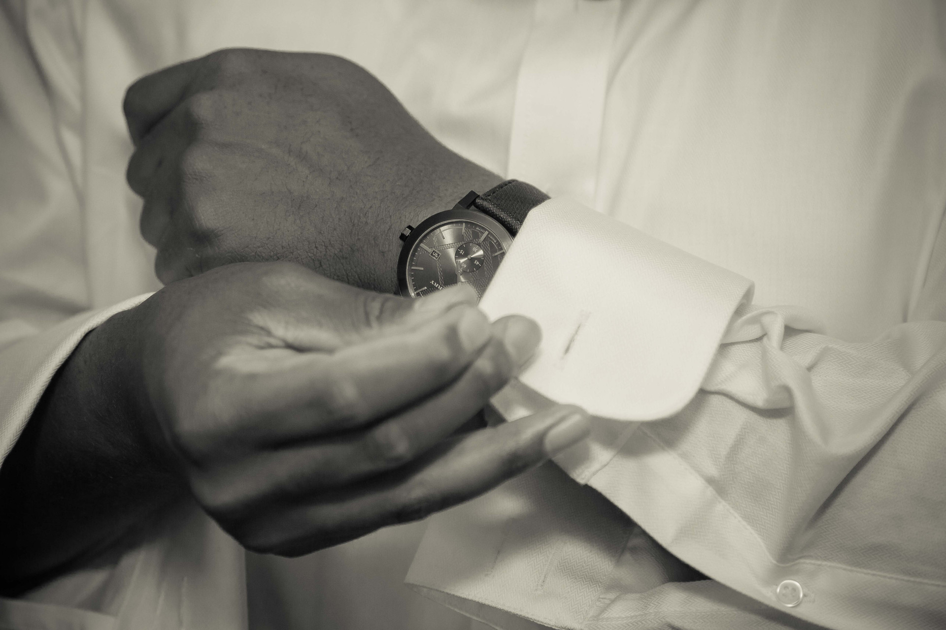 Groom buttoning his sleeve
