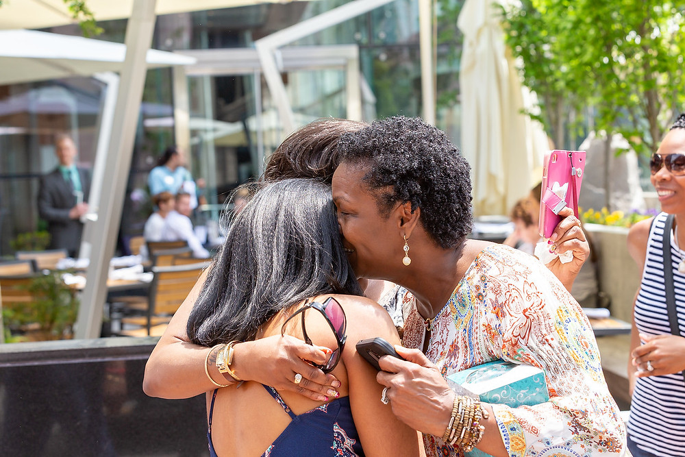 De'Shera hugs her mother and aunt after Nic's classic proposal in downtown Norfolk, VA.
