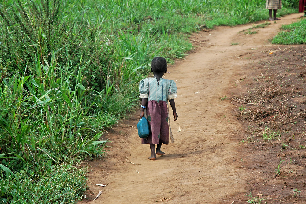 Ugandan Girl Carries Jerry Can On A Dirt Path.jpg