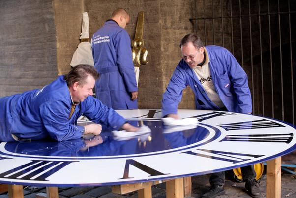 Mitarbeiter beim Polieren eines Zifferblattes vor der Montage