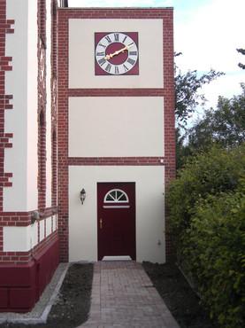 Privatanwesen mit quadratischer Turmuhr über Eingangsbereich