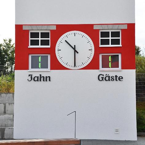 Originalgetreue Abbildung der ehemaligen Fußballuhr am Regensburger Jahn Turm. Diese Uhr verfügt heute am neuen Regensburger Jahnstadion über ein klassisches, mit einem 230V Motor ausgestattetes Fassadenzeigerwerk für freigehende Zeiger.