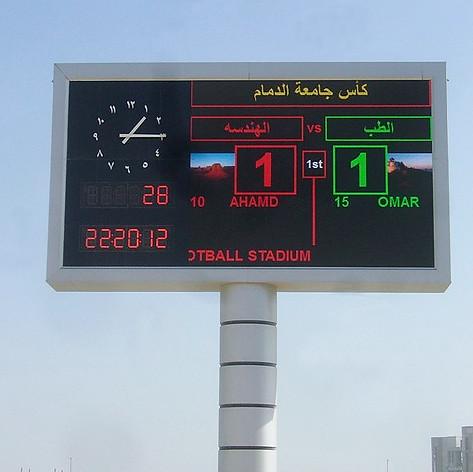 Analoge Stadionuhr integriert in eine ca. 12 x 6 m große digitale Fußballanzeige, Durchmesser von 2 m. Die arabischen Ziffern wurden einzeln aufgesetzt und die Zeiger sind freigehend.