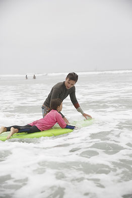 Girl on surfboard getting a surfing lesson