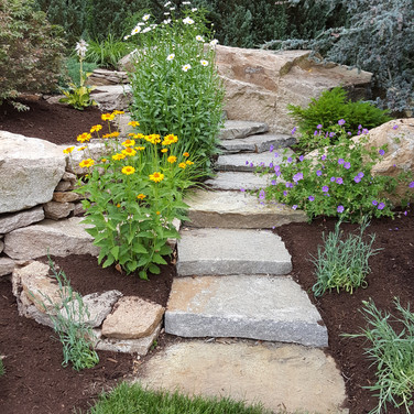 Winding custom natural steps leading you up a hill through a garden.