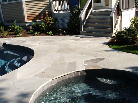 Mosaic stone patio pool surround made of quartz flagging