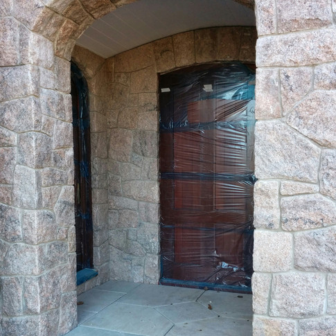 Stone archway and covered entrance area.  Doors were protected during stone installation.