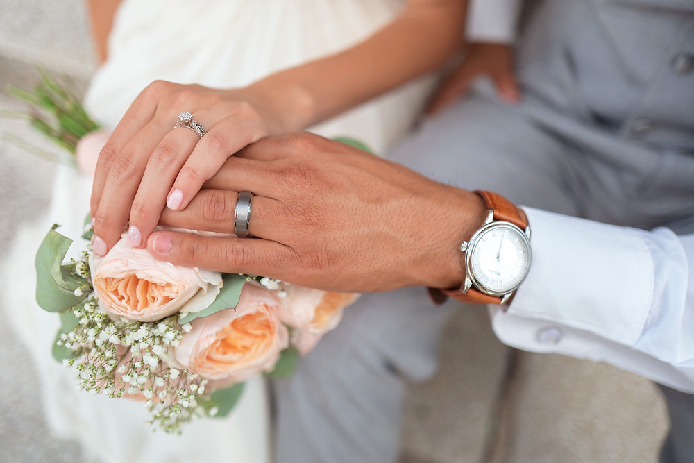 Bride and Groom with wedding rings and peach bouquet