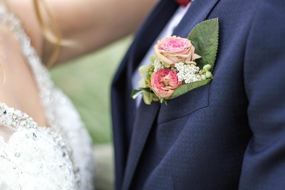 Wedding buttonhole on wedding suit with beaded wedding dress