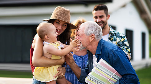A grandfather is playing with a baby and other adults representing estate planning services.