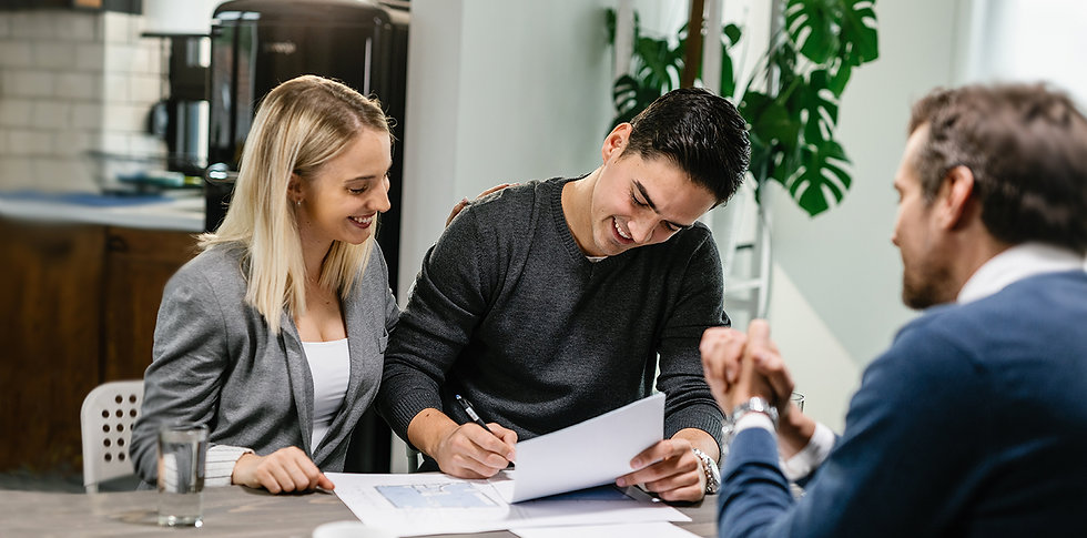 A young couple signing papers at a real estate closing with a Schum & Werner attorney