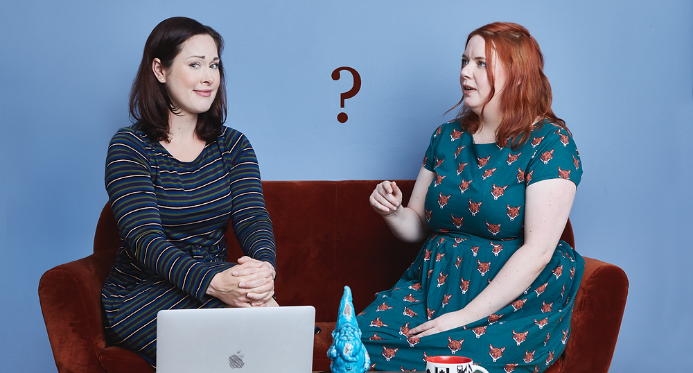 Two women (owners of Copy That) sitting on a couch, looking puzzled.