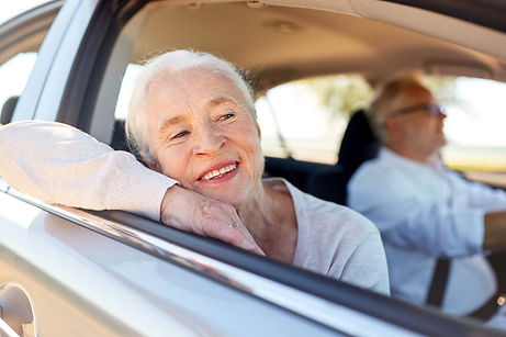 Older woman smiling while leaning on passenger window in car