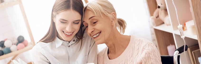 Older woman sitting with younger woman looking at a photo album together