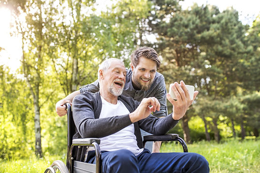 Smiling older man in wheelchair looking at phone with young guy pushing him and smiling at the phone