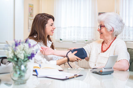 Older woman getting blood pressure measured by nurse while seated at kitchen table