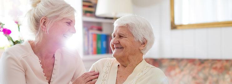 Older woman smiling up at her caregiver