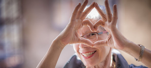 Older woman looking through her hands in a heart shape