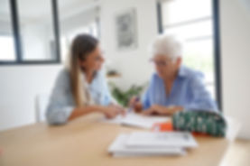 Older woman receiving help with paperwork in an office with a younger female