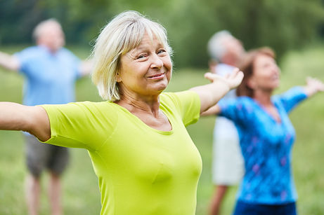 Older woman stretching and smiling during an exercise class outside
