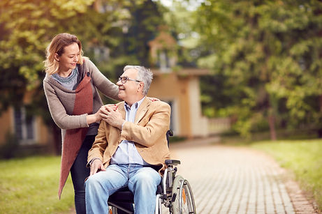 Older man in wheelchair smiling up at female caregiver