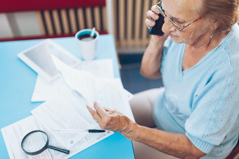 older adult female on phone looking over paperwork