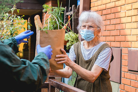 Older woman wearing mask accepting a bag of groceries outside of her house
