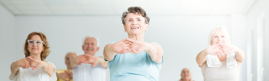 Group of older adults stretching in a fitness class